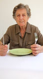 An old woman shows that she is ready to eat Royalty Free Stock Photography