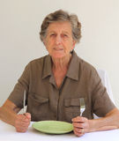 An old woman shows that she is ready to eat Royalty Free Stock Photos
