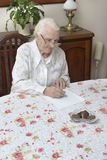 The old woman signs documents sitting at the table. The old woman writes handwritten will Stock Images