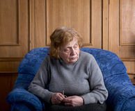 The old woman sits in an armchair Royalty Free Stock Image