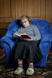 The old woman sits in an armchair and reads Stock Images