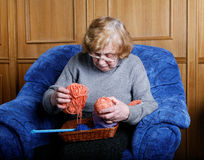 The old woman sits in an blue armchair Stock Images