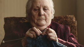 The old woman sits at home and knits garments stock footage