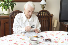 The old woman sits at a table with a newspaper. Grandmother reading a newspaper holding a magnifying glass Royalty Free Stock Image