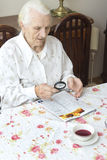 The old woman sits at a table with a newspaper. Grandmother reading a newspaper holding a magnifying glass Stock Photo