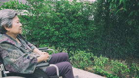 Old woman sitting alone in a wheelchair out in the garden. Stock Photography