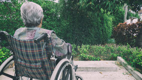 Old woman sitting alone in a wheelchair out in the garden. Royalty Free Stock Images