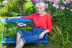 Old Woman Sitting on the Bench at the Garden. Old Woman in Casual Clothing Sitting on the Blue Wooden Bench at the Garden Looking at the Camera Royalty Free Stock Photography