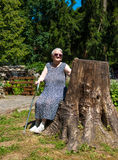 Old woman sitting on a bench. At summer park Royalty Free Stock Photos