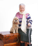 Old woman sitting on a box with a dog. On a white background Royalty Free Stock Photography