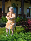 Old woman sitting on a chair with a cane Royalty Free Stock Photos
