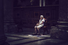 Old woman sitting in colored light on church bench