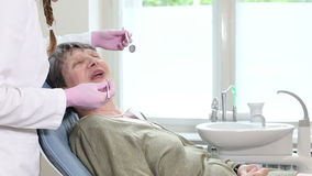 Old woman sitting in dental chair and having routine dental checkup stock video footage