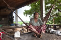 Old woman sitting on a hammock stock photo