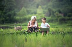 Old Woman Sitting Beside Her Grandson Stock Images