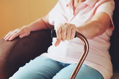 Old woman sitting with his hands on a walking stick. Senior people health care. Stock Photography