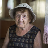 An old woman sitting in his house. Grandmother. Stock Photos