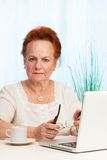 Old woman sitting with laptop Royalty Free Stock Photo