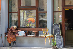 Old woman sitting near entrance of restaurant in Lviv, Ukraine Royalty Free Stock Photos