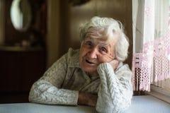 Old woman sitting near the window stock photos