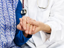 Old woman sitting side by side doctor stroking hands. Old women with blue apron sitting with a doctor beside each other and stroking hands Stock Image