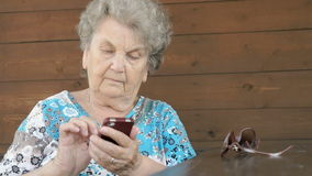 Old woman sitting at the table holds a smartphone stock video footage