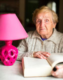 An old woman sitting at the table and reading a book. Active aging Stock Images