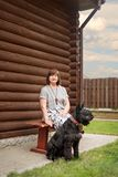 An elderly woman is sitting on a village bench with a black schnauzer near a wooden house in the countryside royalty free stock photography