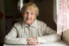 Old woman sitting in a village house. Royalty Free Stock Photos