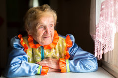 Old woman in Slavic ethnic costume sits at a table Stock Photo