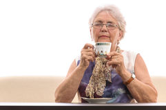 Old woman smelling cup tea Stock Image
