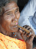 Old woman smokes a cheroot Stock Photos