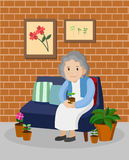 Old woman on the sofa in living room. Old woman with plant pot sitting on the sofa in living room Stock Images