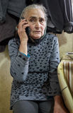 Old woman speaking on mobile phone Stock Images
