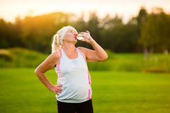 Old woman with sports bottle. Stock Photos