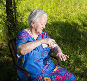 Old woman spraying insect repellent Royalty Free Stock Image