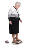 Old woman standing on a bathroom scales Royalty Free Stock Image