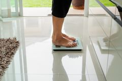 Old woman standing on weight scale in living room royalty free stock photography