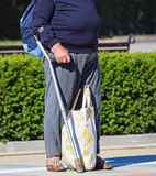 Old woman stands with a cane on the street Stock Photos