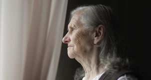 An old woman stands by the window and holds the curtain.