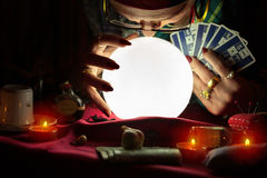 Old woman staring at crystal ball and holding a tarot cards Stock Photo