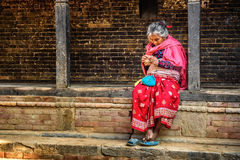 Old woman in the street of Bandipur, Nepal. BANDIPUR, NEPAL - OCTOBER 22, 2015 :  Old woman begs in the street of Bandipur Stock Photo