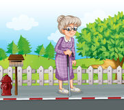 An old woman at the street with a cane standing near the mailbox Royalty Free Stock Image