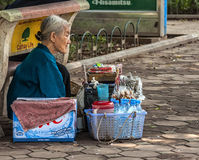 Old woman street vendor selling water while sitting on her haunc Royalty Free Stock Photos