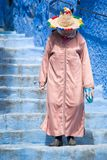 An old woman strolls through the streets of Chefchaouen, the blue town in Morocco, with her traditional costume stock photography