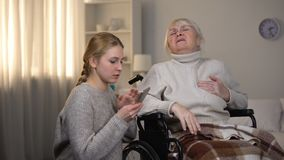 Old woman suffering from heart attack asking granddaughter to call ambulance. Stock footage stock footage