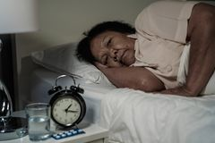 Old woman suffering from insomnia is trying to sleep in bed. At night Royalty Free Stock Photography