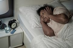 Old woman suffering from insomnia is trying to sleep in bed. At night Royalty Free Stock Images