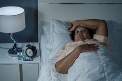 Old woman suffering from insomnia is trying to sleep in bed. At night Stock Photo