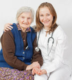 Old woman and the sweet doctor staying together. Old woman and the sweet young doctor Stock Image